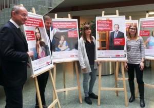 Mit Plakaten Aufmerksamkeit erzeugen: Lea Bührer (rechts) und Maren Wittmann (2. von rechts) stellten ihr Projekt vor. Links Gladbecks Bürgermeister Ulrich Roland und Probst André Müller, Vorsitzender der Caritas Gladbeck.