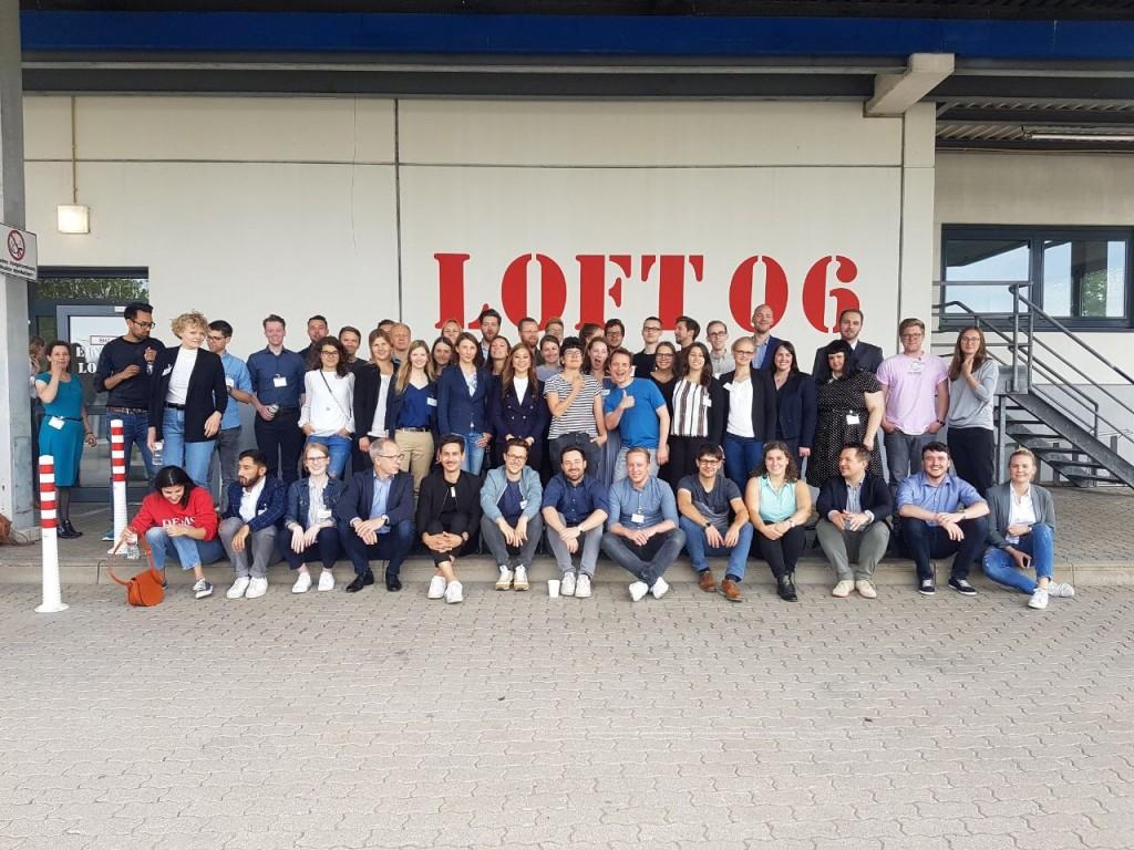 """Alle Teilnehmer des #30u30-Alumni-Barcamps vor der Location """"Loft 06"""" auf dem Gelände der Otto Group."""