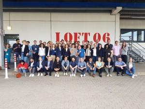 """Alle Teilnehmer des #30u30-Alumni-Barcamps vor der Locatopn """"Loft 06"""" auf dem Gelände der Otto Group."""